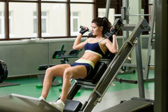 Young pretty woman pumping up muscles with training apparatus Royalty Free Stock Photo