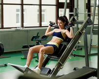 Young pretty woman pumping up muscles with training apparatus Stock Photo