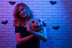 Young pretty woman with pumpkin in hands posing at camera at par. Ty. Free space for text design. Halloween, celebration, party concept stock photos