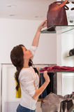 Young pretty woman reaching for a bag on high shelf Royalty Free Stock Image