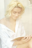 Young pretty woman reading a book in the window Royalty Free Stock Photo