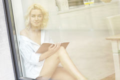 Young pretty woman reading a book in the window Royalty Free Stock Image