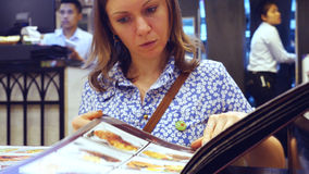 Young pretty woman reading menu in cafe Stock Images