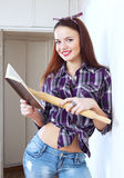 Young pretty woman reads cookbook for recipe Royalty Free Stock Photo