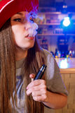 Young pretty woman in red cap smoke an electronic cigarette at the vape shop.  royalty free stock images