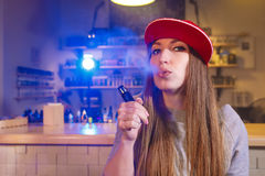 Young pretty woman in red cap smoke an electronic cigarette at the vape shop.  Stock Image