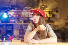 Young pretty woman in red cap smoke an electronic cigarette at the vape shop.  Royalty Free Stock Photos