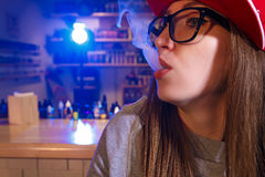 Young pretty woman in red cap smoke an electronic cigarette at the vape shop. Closeup. royalty free stock image