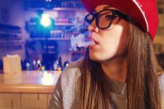 Young pretty woman in red cap smoke an electronic cigarette at the vape shop. Closeup. Stock Photo