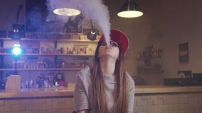 Young pretty woman in red cap smoke an electronic cigarette at the vape shop. Closeup. Slow motion. Young pretty woman in red cap smoke an electronic cigarette stock video