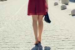 Young pretty woman in red dress walking in the city without shoe stock image