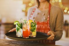 Young pretty woman with red and green cocktails on tray Royalty Free Stock Photos