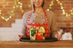Young pretty woman with red and green cocktails on tray Stock Photos