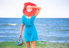 Young pretty woman in red hat relax near blue sea Royalty Free Stock Photography