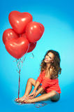 Young pretty woman with red heart shpaed balloons Royalty Free Stock Photos