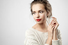 Young pretty woman with red lips. Portrait of a blonde young pretty woman with natural make-up and red lips on gray background Stock Image