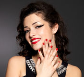 Young pretty woman with red manicure and  lips Royalty Free Stock Image
