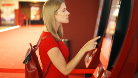 Young pretty woman in red t-shirt buying movie ticket from vending machine at cinema. Young pretty woman in red t-shirt choosing movie and buying ticket from stock video
