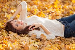 Young pretty woman relaxing in the autumn park. Beauty nature scene with colorful foliage background, yellow trees and leaves stock images