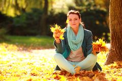 Young pretty woman relaxing in the autumn park Stock Image
