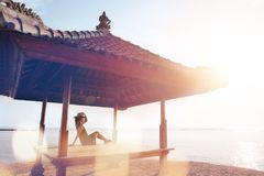 Young pretty woman relaxing in the sun shelter Royalty Free Stock Photo
