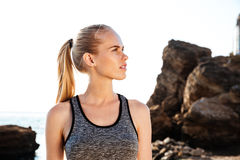 Young pretty woman resting after training on beach at sunset. Young pretty sports woman resting after training on beach at sunset Royalty Free Stock Images