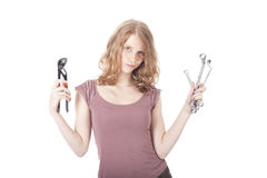 Young pretty woman with ring spanners and pipe wrench Stock Images