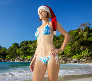 Young pretty woman in santa hat and bikini having fun on beach Royalty Free Stock Images