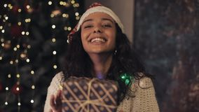 Young pretty woman at santas hat and decorative lights on her neck shaking present box in her hands, looking to camera stock footage