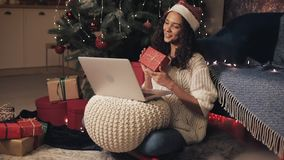 Young pretty woman in santas hat having video call on her laptop. She sitting on the floor at home near Christmas tree stock footage