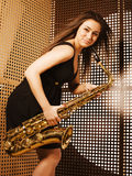 Young pretty woman with saxophone Stock Images