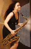 Young pretty woman with saxophone Stock Image