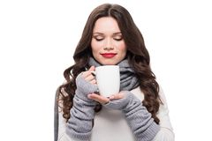 Young pretty woman in scarf and arm warmers smelling coffee,. Isolated on white royalty free stock photo