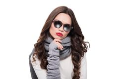 Young pretty woman in scarf and arm warmers, wearing trendy sunglasses and posing with hand on chin,. Isolated on white royalty free stock image