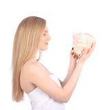 Young pretty woman with seashell, closeup female face portrait. Studio Stock Image