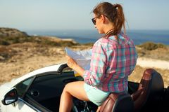Young pretty woman see the map in the cabriolet Stock Image