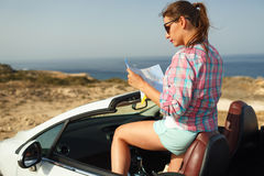 Young pretty woman see the map near the cabriolet Stock Photography