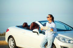 Young pretty woman see the map near the cabriolet Stock Image
