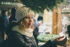 Young pretty woman selecting presents at christmas market Royalty Free Stock Photo