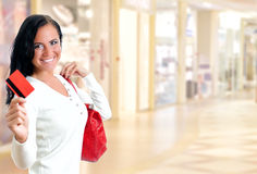 Young pretty woman in shopping center. With credit card Stock Photography