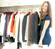 Young pretty woman shopping at mall smiling adorable choosing at rail with diverse clothers, lifestyle people concept Stock Photos