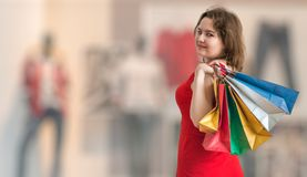 Young pretty woman is shopping. View from behind royalty free stock photos