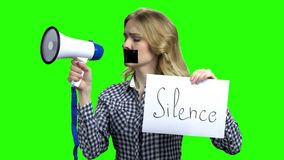 Young pretty woman silenced with tape. Woman activist holding megaphone and card with inscription Silence. Press freedom and censorship stock video footage