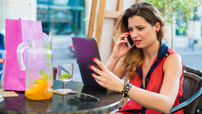 Young pretty woman siting in cafe and holding pad. She is talking on the phone. Royalty Free Stock Photography