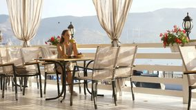Young pretty woman sits in a cafe beholding beautiful views of sea bay. Royalty Free Stock Photos