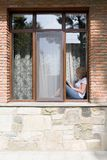 Young pretty woman sits on the windowsill and reads a book. View from the street royalty free stock image