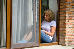 Young pretty woman sits on the windowsill and reads a book. View from the street royalty free stock photography