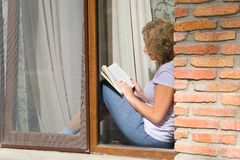 Young pretty woman sits on the windowsill and reads a book. View from the street stock image