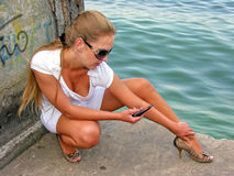 Young pretty woman sitting alone on the pier Stock Photo