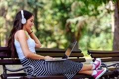 Beautiful young woman with headphones sitting on bench in the park, using laptop computer Stock Photo